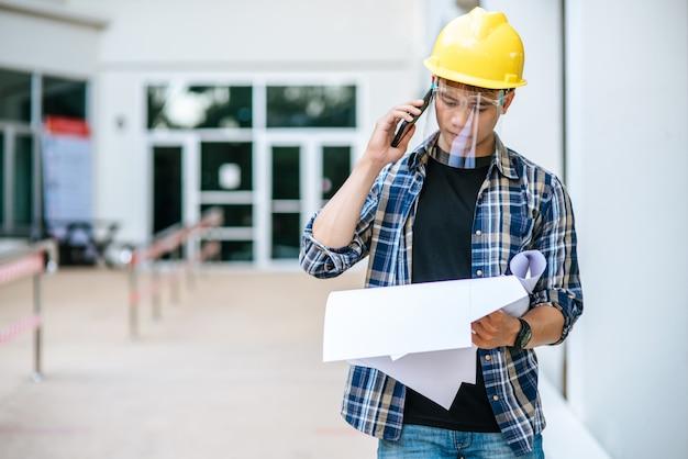 건축가는 평면도를 잡고 전화 통화를합니다.