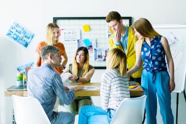 建築家のインテリアデザイナーの創造的な人々マネージャーオフィスワーカーのコンセプトアイデア新しいアパートの設計プロジェクトについて議論します。カラフルな白い部屋でチーム作業ビジネス会議会議プレゼンテーション。