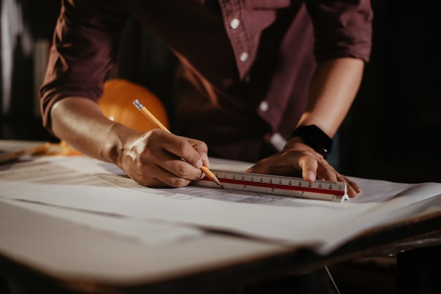 Архитекторы или инженер, держа перо, указывая архитекторов оборудования на ноутбуке с на архитектурном проекте на строительной площадке на столе в офисе.
