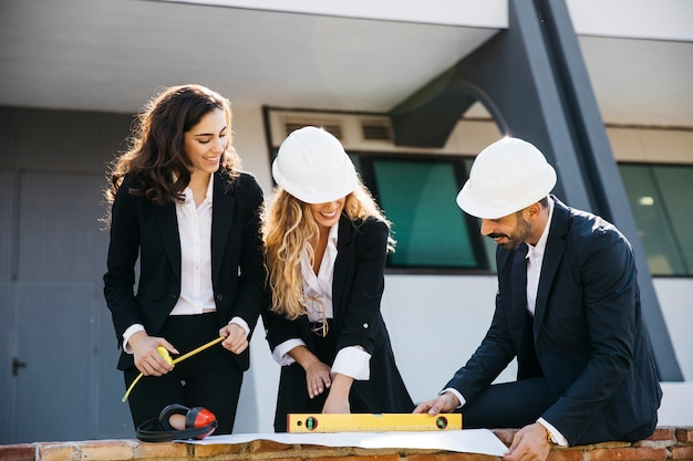 Architects wearing helmets with plan
