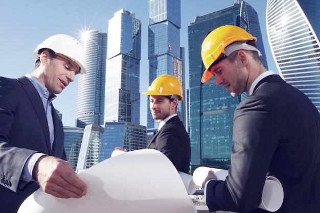 Архитекторы с планом, глядя на небоскребы