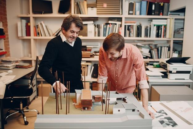 設計図とオフィスビューローでのレイアウト設計プロジェクトを持つ建築家