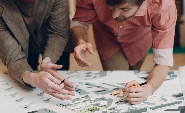 Архитекторы с чертежами и дизайн-проектом макета в офисе архитектурного бюро