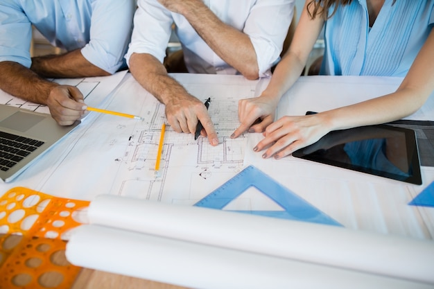 Architects working over blueprint in conference room