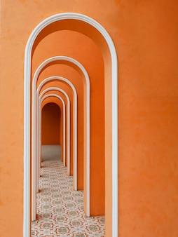 Архитектурный арочный коридор оранжевого цвета с пустой стеной и арабским рисунком плитки.