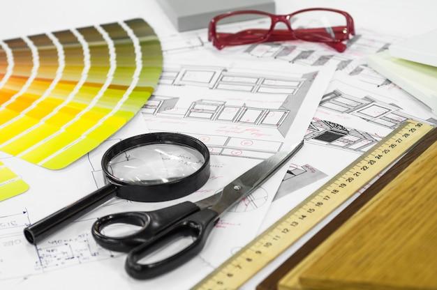 Архитектурный чертеж интерьера с образцами дерева и бумаги, разноцветной палитрой и инструментами для рисования