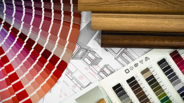 Architectural blueprint interior with wooden and paper samples and a multi-colored palette and draw tools