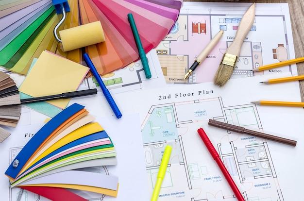 Архитектурная концепция - план дома, образцы цвета и дерева, кисть и рабочие инструменты.