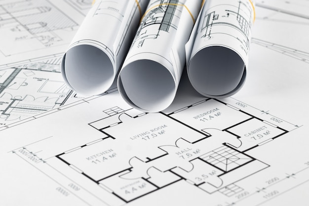 Architectural construction drawings twisted into a roll, construction projects on paper.