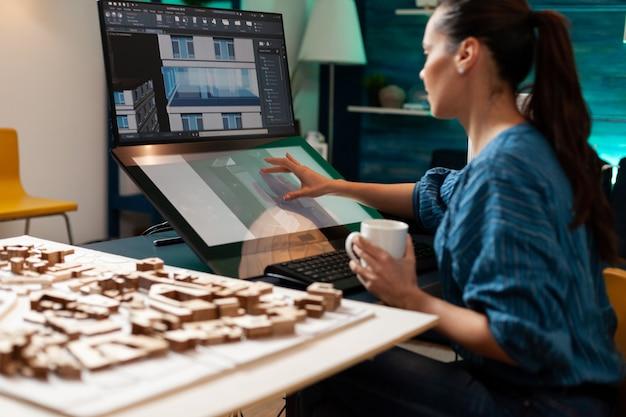 설계 작업장에서 터치패드 화면 기술 모니터 컴퓨터를 사용하여 엔지니어링 스케치를 하는 건축 디자이너. 리노베이션 프로젝트를 위한 건물 계획을 진행 중인 백인 여성