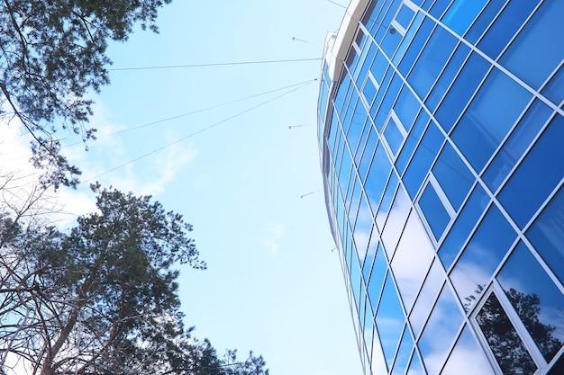他の建物と太陽の複数の反射を伴うファサードの建築の詳細。モダンな建物の外観。建築の抽象的な背景