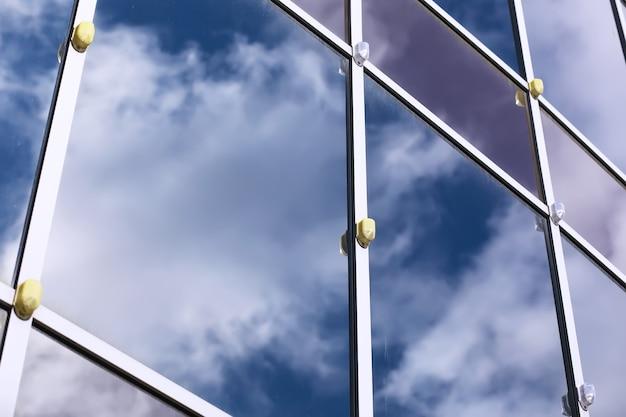 Архитектурная деталь фасада с множественными отражениями других построек и солнца. внешний вид современного здания. архитектура абстрактный фон
