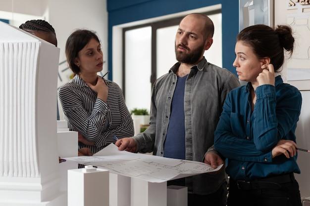 Архитектурная разнообразная рабочая группа, говорящая о проектировании проекта строительства, многоэтническом профессиональном