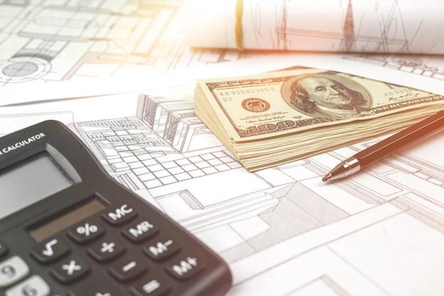 オフィスの机の建設現場での建築プロジェクト。家を建てる費用を計算する