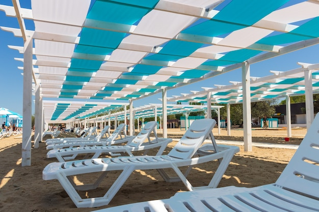 Architectural structures made of wood and white sun beds on the black sea beach