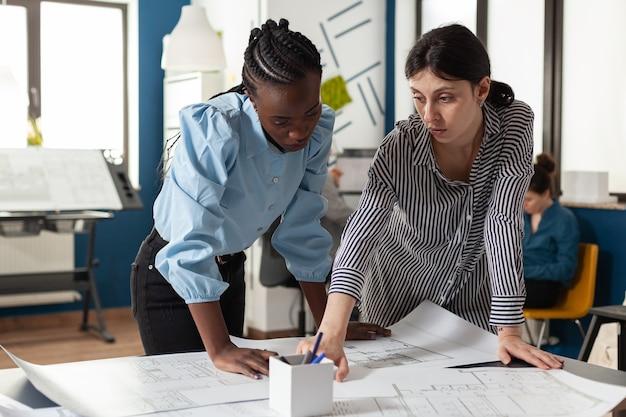 多民族の女性の建築チームは、設計プロジェクトの構築のためのスケッチの青写真のレイアウトを計画します
