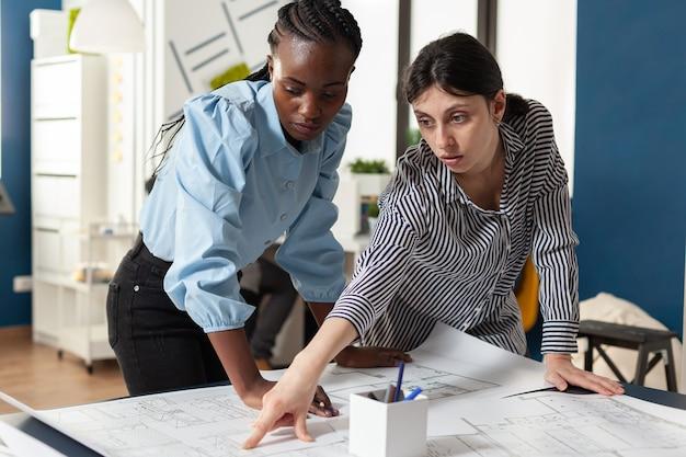 多民族の女性の建築チームはスケッチを計画します