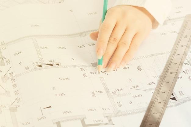 建築と建設。建築家はオフィスで働き、インテリアデザインのスケッチを作ります