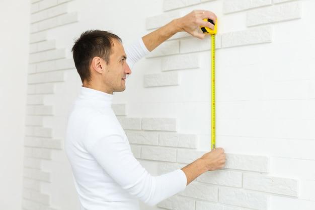 건축 및 주택 개조 개념 - 유연한 눈금자로 벽을 측정하는 남성 건축가