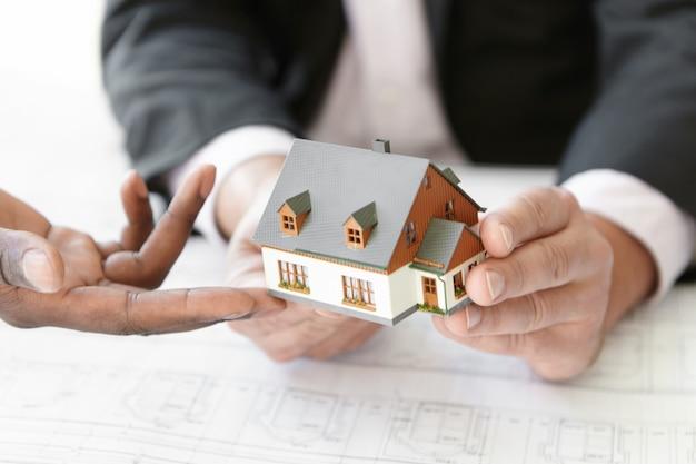 건축, 건축 및 건설 개념. 새 주택 프로젝트의 설계를 평가하는 두 엔지니어의 자른 샷입니다.