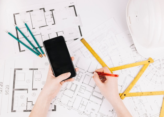 Architecture concept with building plan and smartphone