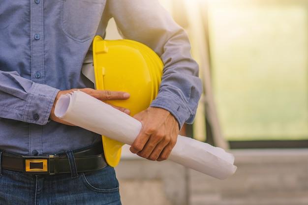Инженер-архитектор, держащий каску на строительном фоне сайта
