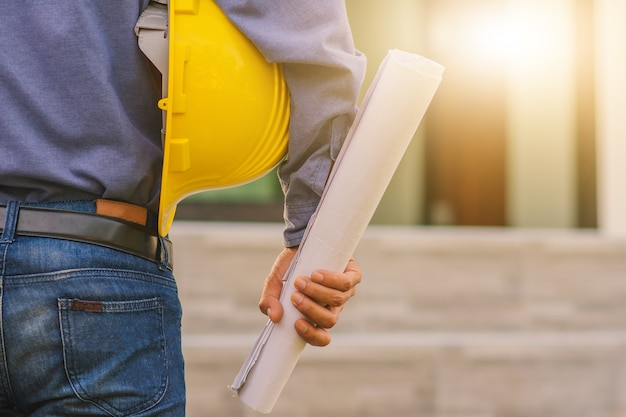 Architecture engineer holding hard hat on site building construction background
