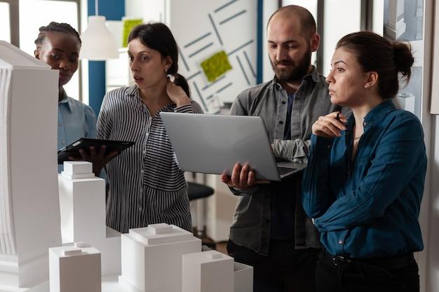 ラップトップコンピュータータブレットの青写真計画を分析するオフィスで会議を行う建築多民族労働者。マケット建築モデルプロジェクト設計建設に取り組んでいるグループ