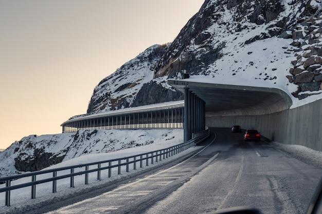 Архитектура туннельной дороги с автомобилем, проезжающим через снежную гору зимой на лофотенских островах, норвегия