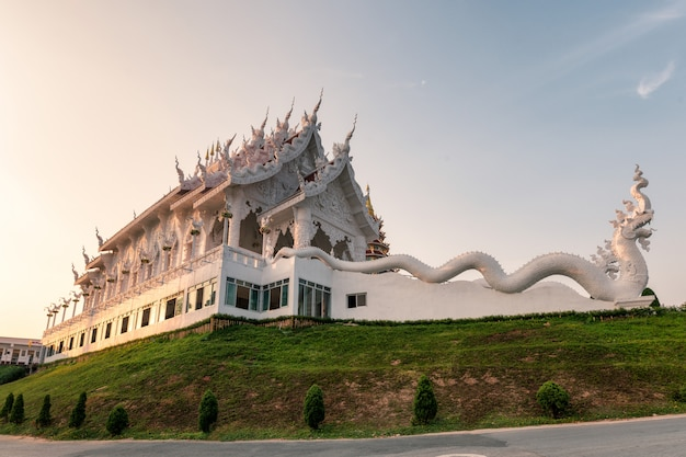 Architecture white church with dragon statue on hill in evening at wat huay pla kang