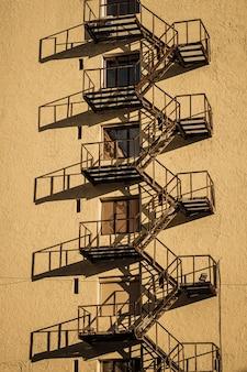 金属製の非常階段の影と建築の白い高層オフィスビル