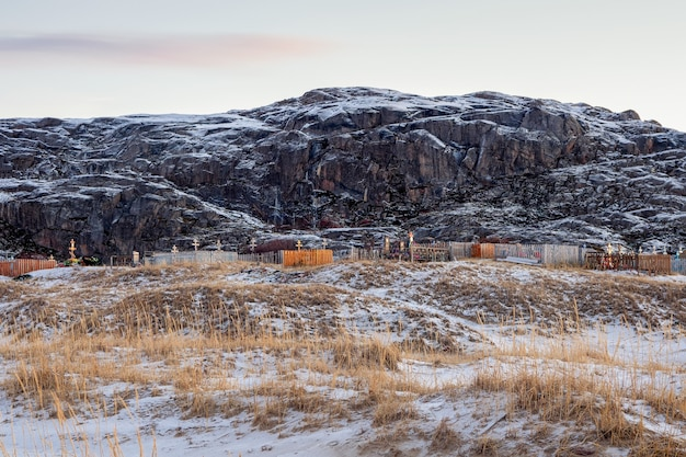 Arctic cemetery.  cemetery on the background of hills on the arctic coast in teriberka. russia.