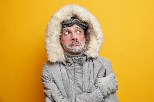 北極の挑戦。凍った男は冬の極度の凍結中に震え、上は暖かいジャケットを着ており、赤い顔は霜で覆われています。