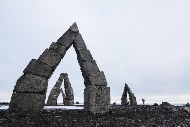 アイスランドの曇り空の下で雪に覆われたフィールドに囲まれた北極のヘンジ