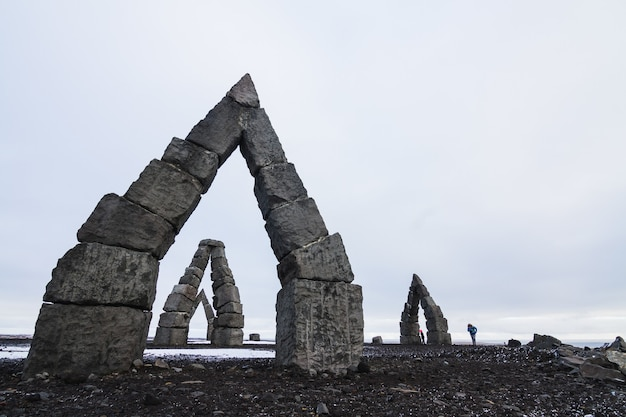 Arctic henge surrounded by a field covered in the snow under a cloudy sky in iceland