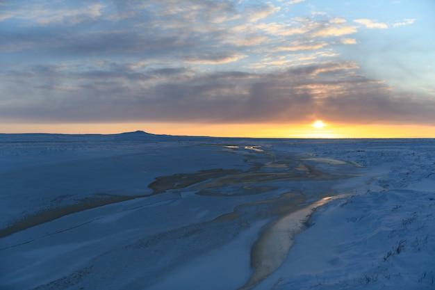 冬の北極の風景。ツンドラの氷と雪の草。日没。