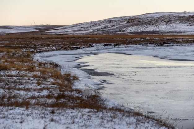 Arctic landscape in winter time. small river with ice in tundra.
