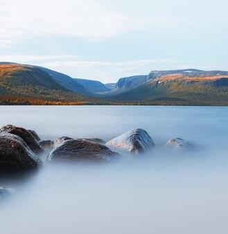 北極圏の野生生物ツンドラ湖の前景に石があり、背景がぼやけています。