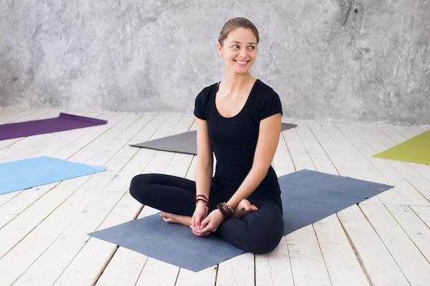Йога молодой привлекательной женщины практикуя, сидя в тренировке ardha padmasana, половинное представление лотоса.