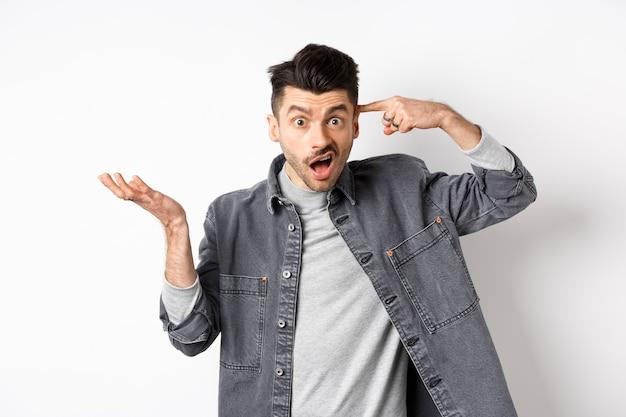 ばかじゃないの。愚かな行動のために人を叱る怒っている男、頭のこめかみを指して手を上げると混乱し、白い背景の上に立っている間不平を言う。