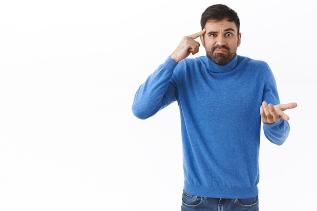 Are you dumb or crazy. annoyed and bothered, frustrated bearded man scolding person for saying stupid things, acting strange, roll finger on temple and raise hand in dismay, white wall