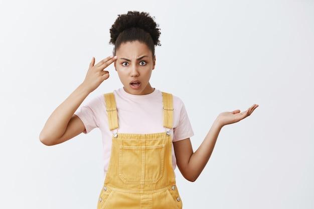 あなたは正気か、ばかですか。黒い肌の不快な腹を立ててイライラした質問のある女性の肖像画、手のひらを広げて肩をすくめて、寺院の近くで指を握り、愚かでクレイジーな誰かを見つめる
