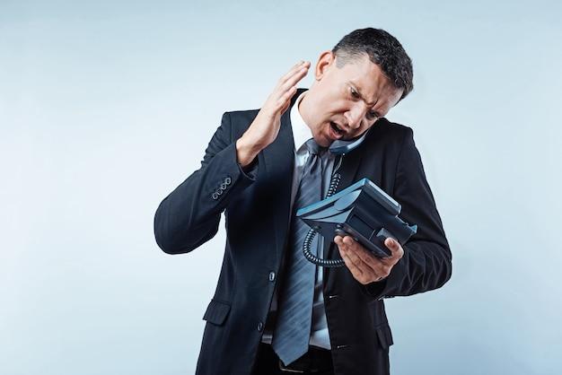 농담 해. 밝은 배경 위에 비즈니스 전화 대화 중 몸짓과 화가 점점 비즈니스의 긴장 남자.