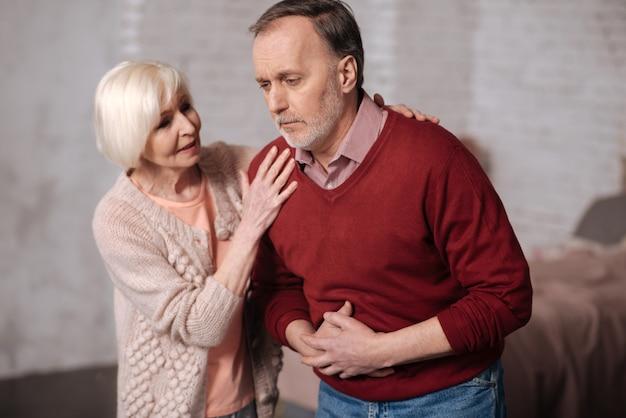 大丈夫ですか。ひどい腹痛で先輩夫の近くに立って支えているかなり年配の女性。