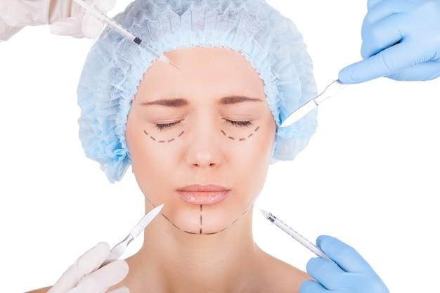 変更の準備はできていますか?注射器とナイフを顔の近くに保持している医療用手袋の4つの手で目を閉じている恐怖の若い女性