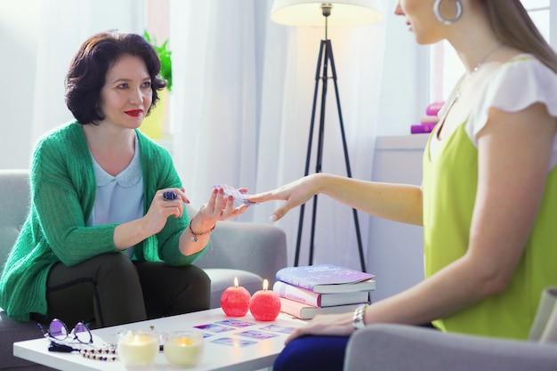 Вы готовы. позитивная милая женщина улыбается своему клиенту, будучи готовой сказать будущее