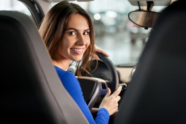 갈 준비가 되있어? 카메라를 보고 차 앞 좌석에 앉아 매력적인 젊은 여자