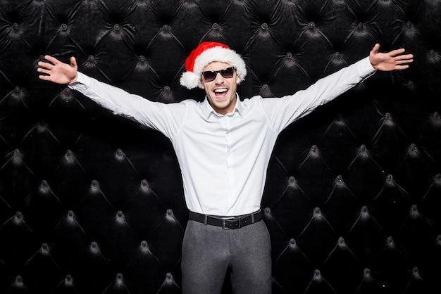 즐길 준비가 되셨나요? 선글라스를 끼고 산타 모자를 쓴 잘생긴 청년이 손을 뻗고 검은 배경에 서서 긍정적인 표정을 짓고 있다