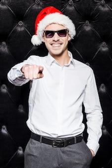 파티할 준비가 되었나요? 선글라스와 산타 모자를 쓴 잘생긴 청년이 당신을 가리키며 검은 배경에 서서 웃고 있습니다