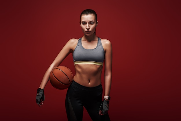 스포츠우먼이 빨간색 배경 위에 공을 서 있는 훈련을 하고 있습니까?